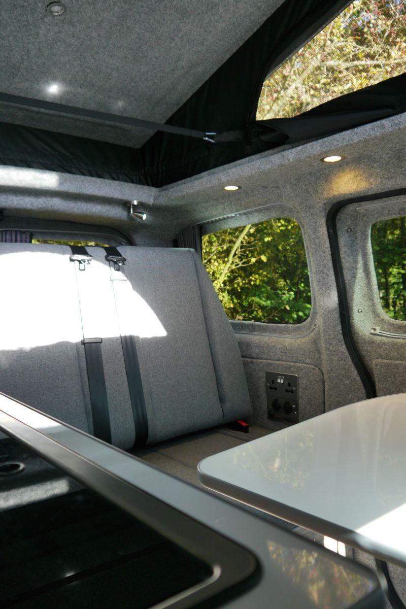 Silver NV200 CamperCar grey seats Sussex Campervans kitchen to rnr bed seat.JPG
